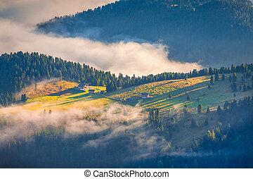 Foggy summer sunrise in the Italian Alps.