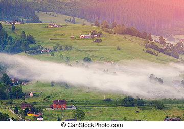 Foggy summer sunrise in the mountain village