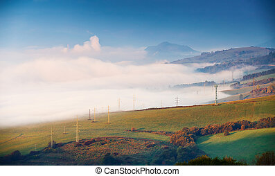 Foggy sunny morning in mountain. Misty hills. Town in valley.