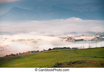 Foggy sunny morning in mountain village. Misty hills