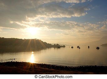 Foggy sunrise landscape photo with boat, mountain in the morning