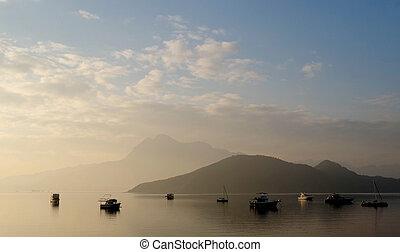 Foggy sunrise landscape photo with boat, mountain