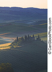 Foggy sunrise over the rural house with vineyards in San Quirico d'Orcia, Tuscany, Italy