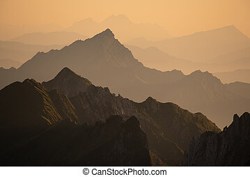 Foggy sunset with beautiful silhouette of mountain range in Switzerland