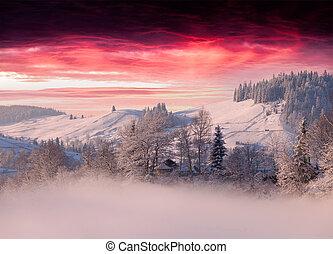 Foggy winter landscape in mountain village ander the dark red sky