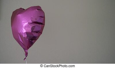 Foil Heart colorful balloon o ngrey wall background 4k -...