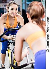 folâtre, cyclisme femme, gymnase, intérieur, jeune, pendant, pedaling