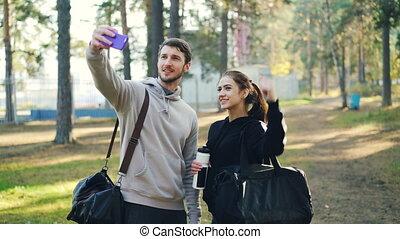 folâtre, sacs, smartphone, extérieur, appareil-photo., gens, selfie, pratique, jeune, park., femme, poser, tenue, utilisation, homme, amis, prendre, après, heureux