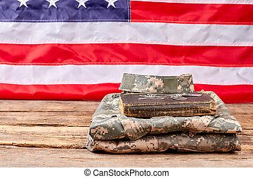 Folded army uniform with book and dog tags.