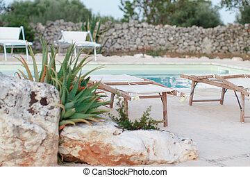 Folded deck chairs near a swimming pool in a garden