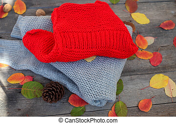 Folded knitted things, autumn leaves on a wooden background.