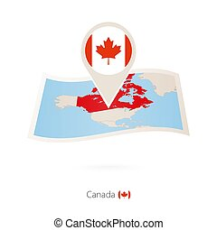 Folded paper map of Canada with flag pin of Canada.