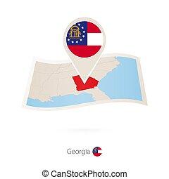 Folded paper map of Georgia U.S. State with flag pin of Georgia.