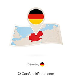 Folded paper map of Germany with flag pin of Germany.