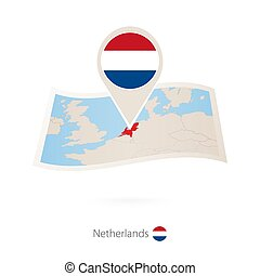 Folded paper map of Netherlands with flag pin of Netherlands.