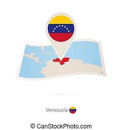 Folded paper map of Venezuela with flag pin of Venezuela.