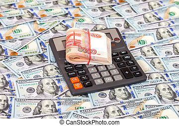 Folded stack of russian roubles and calculator on dollars background
