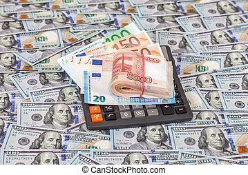 Folded stack of russian roubles, euro banknotes and calculator on dollars background