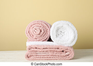 Folded towels on white wooden table against beige background, space for text