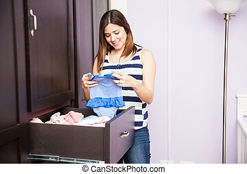 Folding baby clothes in a closet