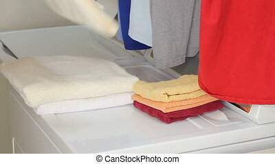 Folding Laundry - Arms and hands of a male come in from the...