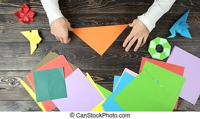 Folding origami paper in triangle, top view. Man making...