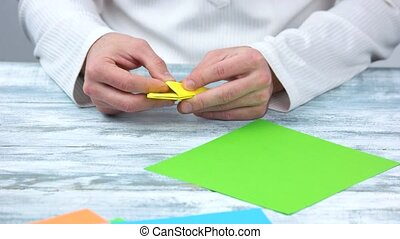 Folding paper, creating origami figure. First step of making...