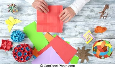 Folding red origami paper. Top view, origami figures on...
