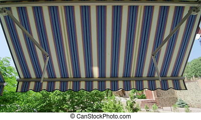 Folding retractable awning mounted onto the outside wall of...