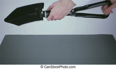 folding shovel in the hands of a businessman
