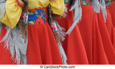 Folk art collective in ethnic Ukrainian national costumes cheerfully sing folk songs and dance.