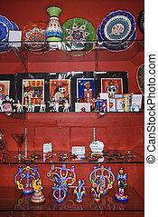 Shelves of unique folk art in retail store.