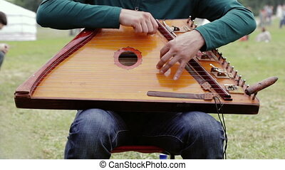 Folk musician playing gusli