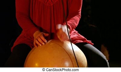 Close up footage of a lady drummer playing a calabash, an instrument originating from Africa, made from a large dried and hollowed gourd vegetable.