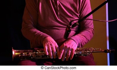 Close up shots of an alto saxophone player performing a set inside a rhythm and blues music bar. Low lighting sets the atmosphere.
