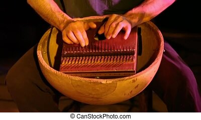 Hands of a musician are seen closeup playing a kalimba aka sanza, a traditional thumb piano instrument used in African music. Seen in a cozy music bar.