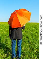 folk, under, en, orange umbrella, in, a, fält, väntan, för, regna
