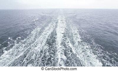 Follow ferry in rains - Foamy wake behind stern ferry in...