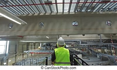 Follow footage of engineers in a hard hat walking through...