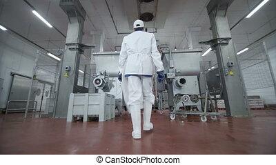 Follow footage of factory worker in cap that is walking...