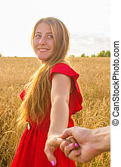 Follow me, Beautiful romantic young woman holds the hand of a man in a wheat field