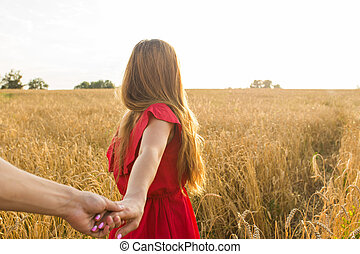 Follow me, Beautiful young woman holds the hand of man in a wheat field