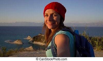 Follow me - happy young woman in a red hat and with a backpack behind her back pulling guy's hand. Hand in hand walking to the Cape Drastis at Corfu island in Greece