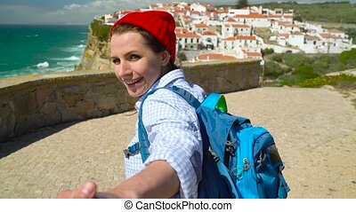 Follow me - happy young woman in a red hat and with a backpack behind her back pulling guy's hand at Azenhas do Mar, Portugal. Hand in hand walking to the ocean coast