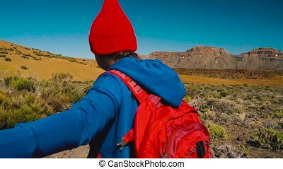 Follow me - happy young woman in red hat with backpack pulling guy's hand. Hand in hand walking throw the Teide National Park, Tenerife, Canary Islands, Spain. Slow motion