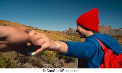Follow me - happy young woman in red hat with backpack pulling guy's hand. Hand in hand walking throw the Teide National Park, Tenerife, Canary Islands, Spain.