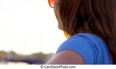 Follow me - happy young woman in sunglasses pulling guy's hand. Hand in hand walking to the marina with a lot of yachts and boats, close up. Slow motion