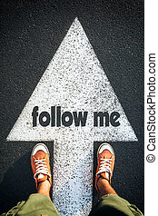 Follow me - Red shoes standing on follow me sign