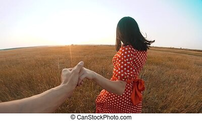 follow me. pretty portrait brunette girl goes with a man by the hand on nature field romance love. slow motion video. girl and man walking call beckoning lifestyle finger. follow me concept