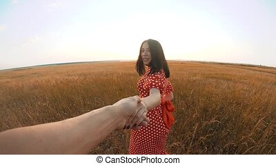 follow me. pretty portrait brunette girl goes with a man by the hand on nature field romance love. slow lifestyle motion video. girl and man walking call beckoning finger. follow me concept